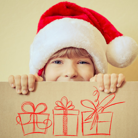 white card: Child holding Christmas card with drawn gift boxes. Xmas holiday concept