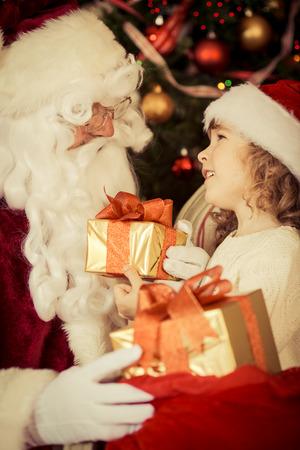 weihnachten vintage: Weihnachtsmann und Kind zu Hause mit Weihnachtsgeschenk Lizenzfreie Bilder