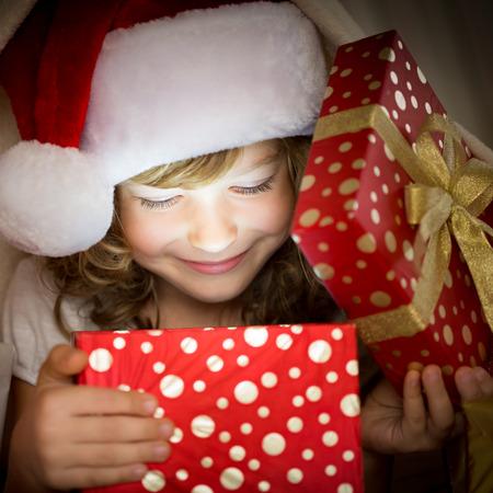 cajas navide�as: Ni�o que sostiene regalo de Navidad. Concepto de vacaciones de Navidad Foto de archivo