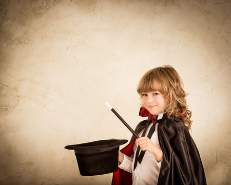 Child magician holding top hat and magic wand. Success concept photo