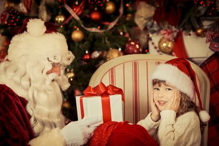 Santa Claus and child at home. Christmas gift. Family holiday concept photo