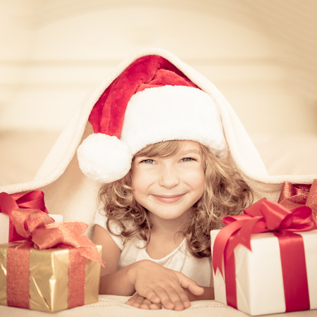 christmas fun: Child holding Christmas gift. Xmas holiday concept Stock Photo
