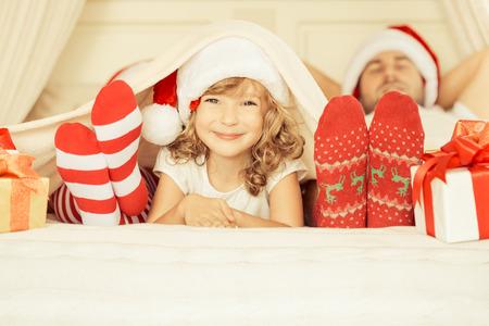 Glückliche Familie zu Hause. Mutter, Vater und Kind mit Weihnachtsgeschenk. Winterurlaub Konzept Standard-Bild