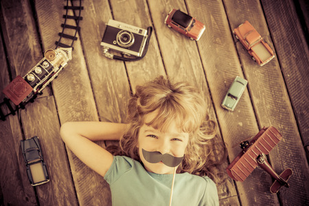 vintage children: Hipster kid with vintage wooden toys at home. Girl power and feminism concept