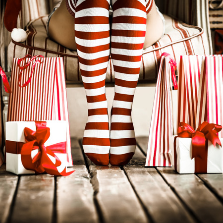 holding a christmas ornament: Sexy woman legs. Christmas concept