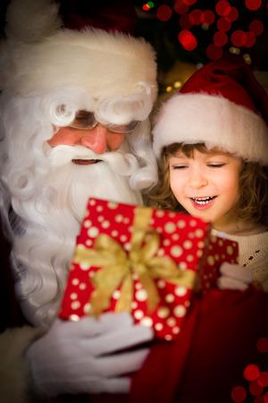 pere noel: Père Noël et de l'enfant à la maison. Cadeau de Noël. concept de vacances de la famille Banque d'images