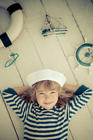 cruise: Happy kid playing with toy sailing boat at home. Travel and adventure concept
