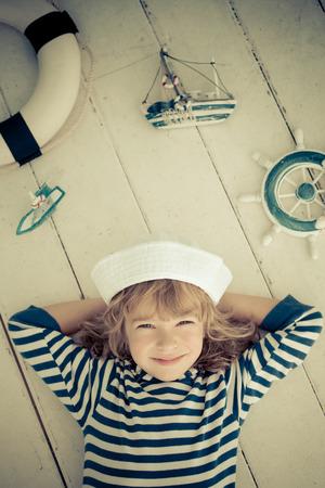 voile: Heureux enfant qui joue avec un bateau jouet de la voile � la maison. concept de Voyage et aventure