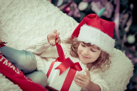 christmas baby: Child holding Christmas gift. Xmas holiday concept Stock Photo