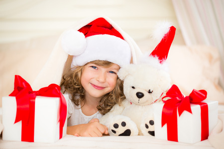Child and teddy with Christmas gift. Xmas holiday concept photo