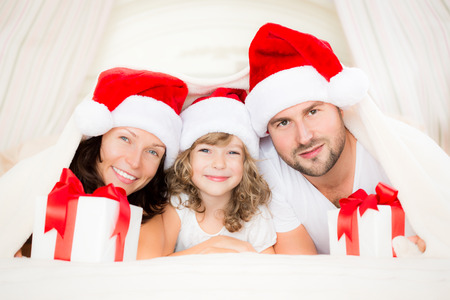 holding a christmas ornament: Happy family with Christmas gift. Xmas holiday concept