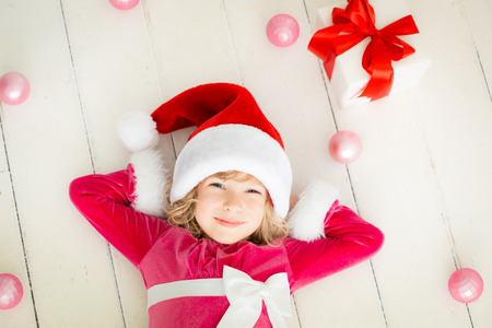 Child holding Christmas gift. Xmas holiday concept