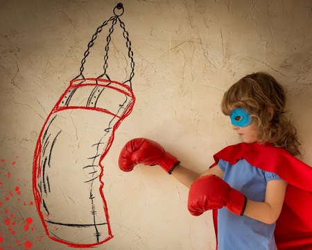 Superhero child dressed in red cape, boxing gloves and blue mask against grunge wall background