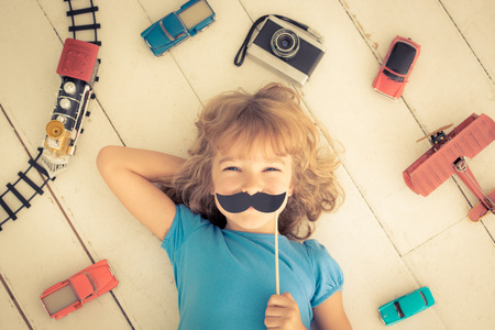 feminism: Hipster kid with vintage wooden toys at home. Girl power and feminism concept
