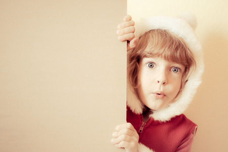 holding a christmas ornament: Child holding Christmas card blank. Xmas holiday concept