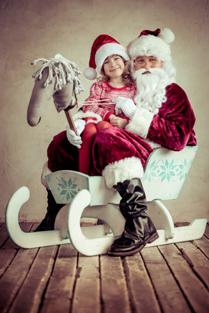 Santa Claus and child sitting on sleigh. Christmas gift. Family holiday concept