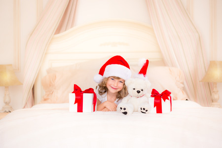 Happy child with Christmas gift. Funny baby dressed in Santa Claus hat. Kid playing at home. Xmas holiday concept photo