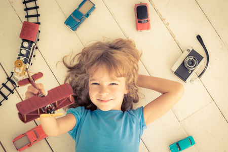 Child playing with vintage toys at home. Girl power and feminism concept