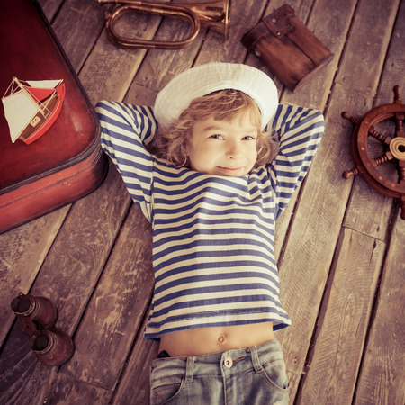 striped vest: Happy kid dressed in sailor. Child playing at home. Travel and adventure concept