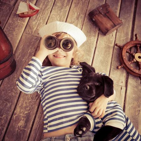 Šťastný kluk oblečený v námořník. Dítě si hraje se psem doma. Cestování a dobrodružství koncepce