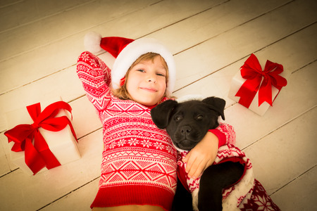 christmas fun: Happy child and dog with Christmas gift. Kid dressed in Santa Claus hat. Baby having fun at home. Xmas holiday concept