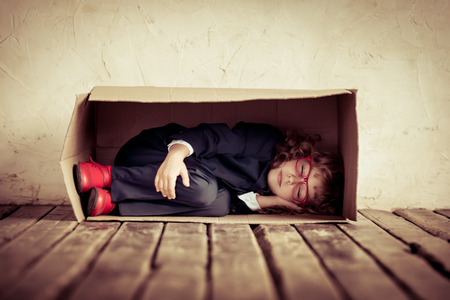 Portrait of young businessman in cardboard box. Think outside the box. Copy space for your text