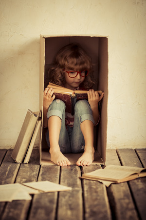 Child sitting in cardboard box. Kid reading book. Freedom and imagination concept