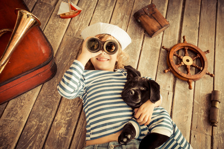 fun: Happy kid dressed in sailor. Child playing with dog at home. Travel and adventure concept
