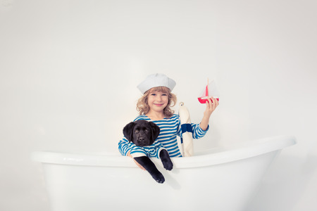 Happy kid dressed in sailor. Child playing with dog at home. Travel and adventure concept