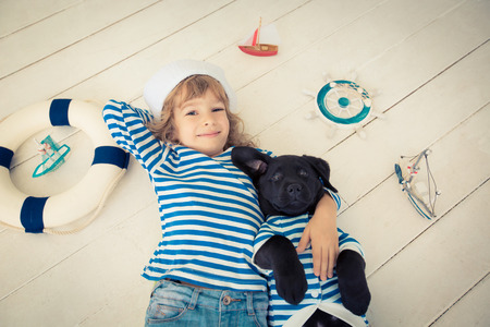 Happy kid dressed in sailor. Child playing with dog at home. Travel and adventure concept photo