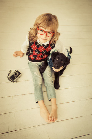 Hipster kid and dog. Child playing at home photo