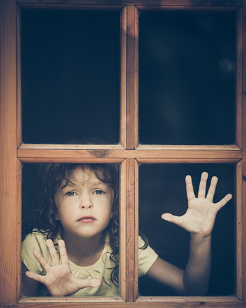 house windows: Sad child at home Stock Photo