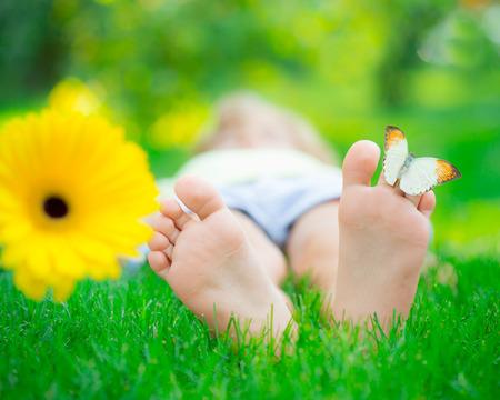 Children feet in green grass. Butterfly on spring flower Stock Photo