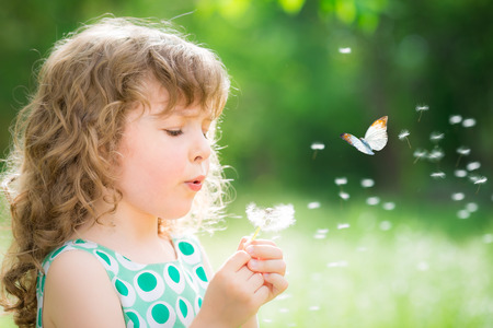 Niño hermoso con la flor de diente de león en la primavera de parque. Cabrito feliz divertirse al aire libre