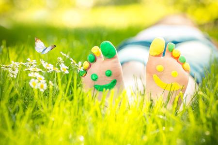 primavera: Ni�o acostado en la hierba verde. Cabrito que se divierte al aire libre en el parque del resorte