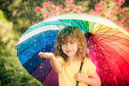 lluvia: Niño feliz en la lluvia. Cabrito divertido jugando al aire libre en el parque de la primavera