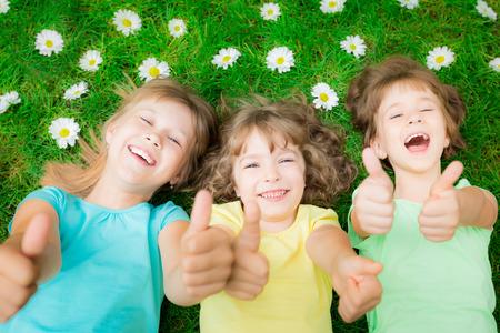 children: Счастливые дети, лежащие на зеленой траве в парке весной. Смеясь дети показывает палец вверх