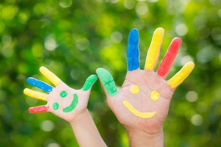 man face: Smiley op handen tegen groene lente achtergrond. Vader en zoon met plezier buitenshuis
