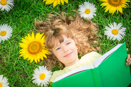 kids reading book: Happy child lying on green grass. Funny kid reading the book in spring park
