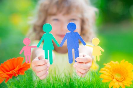 multi ethnic children: Child holding multi ethnic paper family in hands against spring green background
