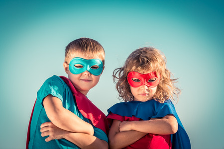 super hero: Superhero children against summer sky background. Kids having fun outdoors. Boy and girl playing. Success and winner concept Stock Photo