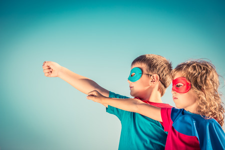 lideres: Niños Superhero contra fondo del cielo de verano. Niños que se divierten al aire libre. Niño y niña jugando. El éxito y el concepto del ganador