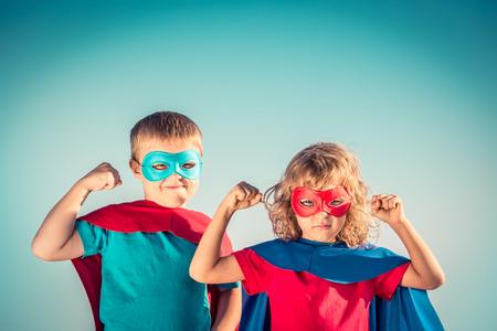 sport team: Superheld kinderen tegen de zomer hemel achtergrond. Kinderen plezier buitenshuis. Jongen en meisje spelen. Succes en winnaar begrip