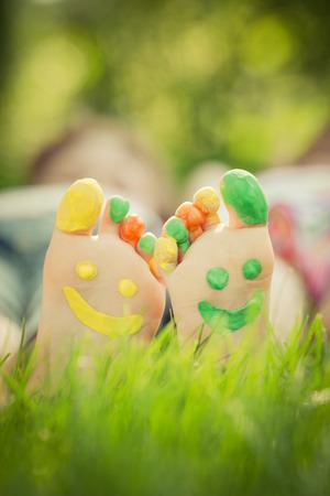 Paar liggend op groen gras. Kinderen plezier buitenshuis in het voorjaar park. Retro afgezwakt Stockfoto