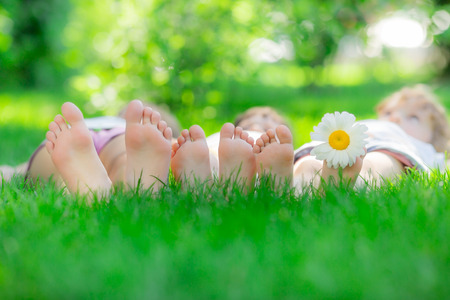Happy family lying on green grass. Children having fun outdoors in spring park photo