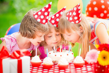 pastel de cumplea�os: Grupo de ni�os felices que celebran cumplea�os. Ni�os que se divierten en el jard�n de primavera