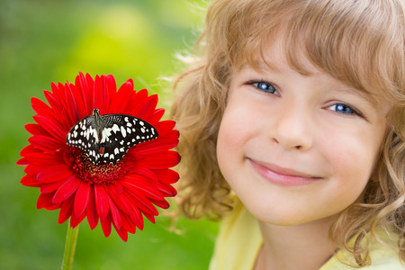 Beautiful child with butterfly in spring park photo