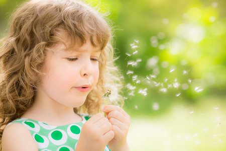 Beautiful child with dandelion flower in spring park Imagens