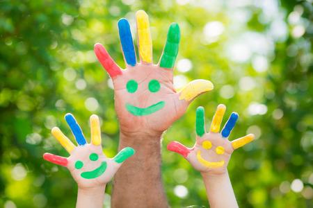 visage homme: Smiley sur les mains contre printemps vert fond Banque d'images