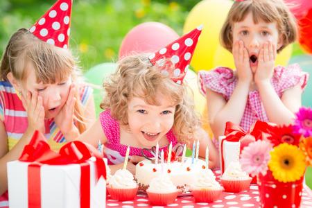 boys party: Group of happy children celebrating birthday in spring garden